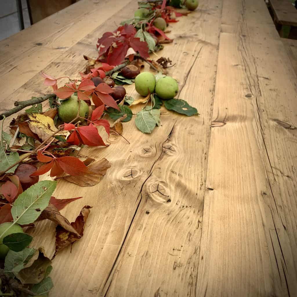 Wooden trestle table for hire decorated in autumnal leaves